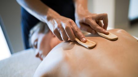 Massagetherapeut die houten hulpmiddel gebruiken om patiënt te masseren