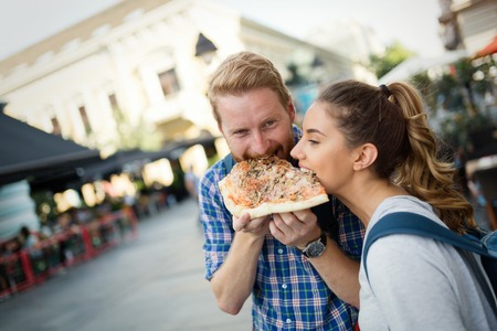 voyage: Happy couple sharing pizza on street