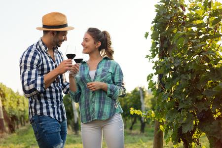 People tasting wine in vineyard