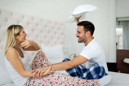 Happy attractive couple play fighting with pillows