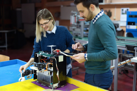 Young students of robotics preparing robot for testing Stock Photo