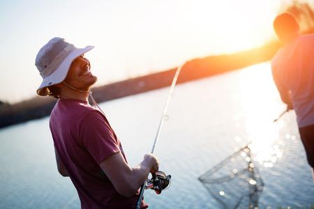 Jonge mens die op een meer bij zonsondergang vissen en van hobby genieten