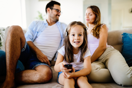 Young girl watching tv with her parents Stock Photo