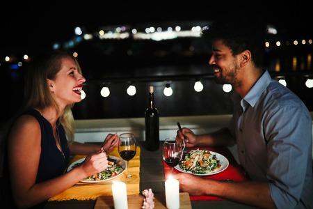 屋上にロマンチックなディナーを持つ若い美しいカップル