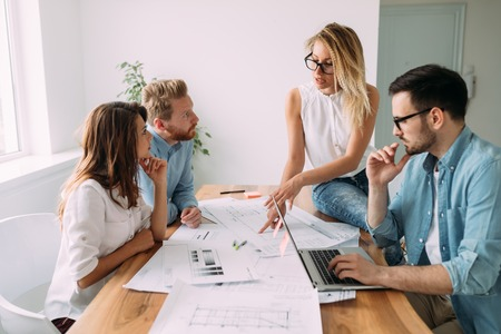 젊은 비즈니스 사람들과 프로젝트에서 작업하는 건축가의 그룹