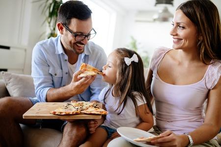 幸せな家族の家で一緒にピザを共有