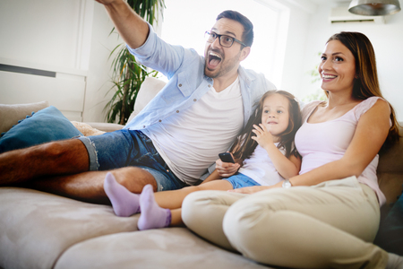 Happy family watching television at their home Stock Photo