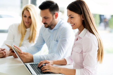 Drie jonge glimlachende collega's die aan laptop samenwerken Stockfoto