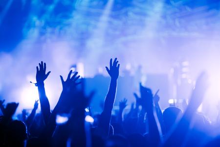 音楽祭での空気中の手で歓声を上げる群衆