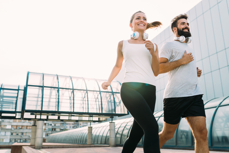 Young fitness couple running in urban area Reklamní fotografie