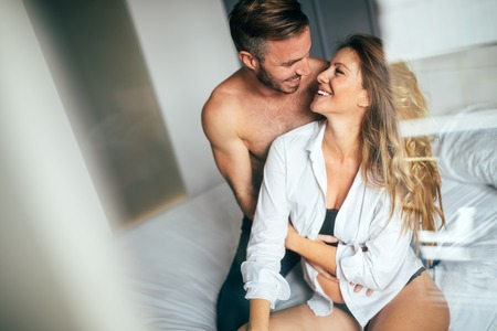 Attractive couple sharing intimate moments in bedroom Stock Photo
