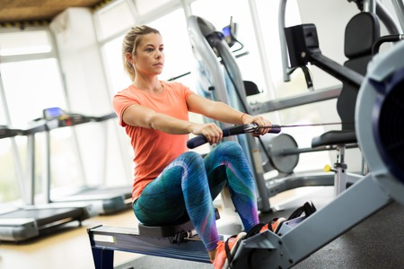 Young blonde woman working on rowing machine 스톡 콘텐츠