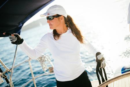 그녀의 보트와 항해하는 매력적인 강한 여자 스톡 콘텐츠