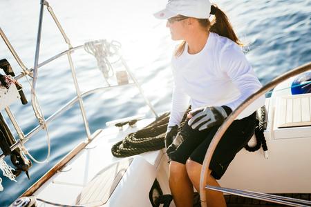 魅力的な強い女性が彼女のボートで航海する 写真素材