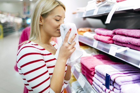 consumerism: Beautiful woman inspecting and buying towels