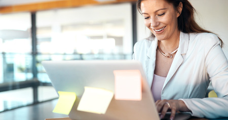 Close-up picture of attractive woman typing on laptop Stock Photo