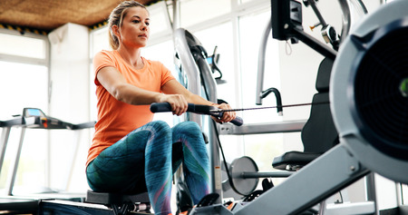 Young blonde woman working on rowing machine Stock Photo