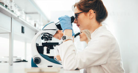 Young scientist looking through microscope in laboratory