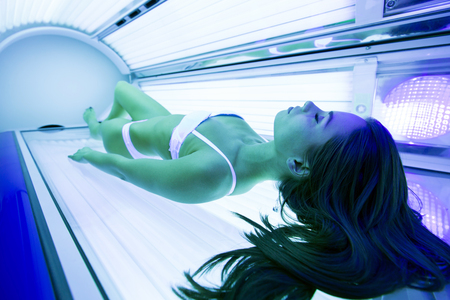 Beautiful brunette sunbathing in solarium Standard-Bild