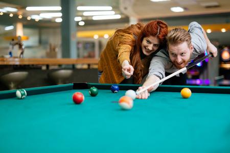 Beautiful couple playing billiards Imagens