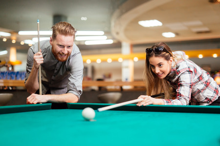 Couple flirting while playing snooker