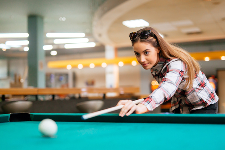 Brunette aiming while playing snooker