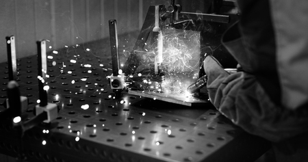 Worker cutting metalsheet by acetylene torch with bright sparks