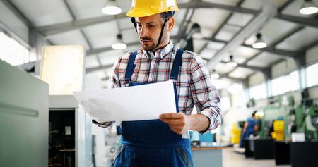 Portrait of an architect builder studying layout plans of plant Stock Photo