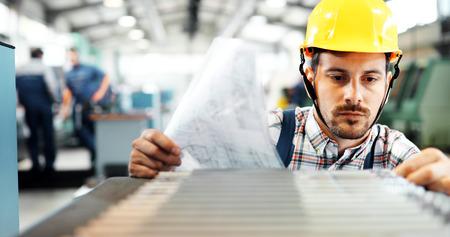 Portret van een knappe ingenieur in een fabriek