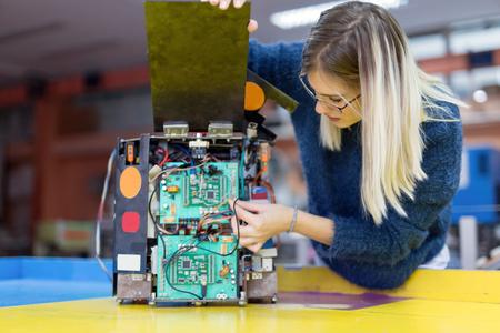 Jonge vrouweningenieur die aan roboticaproject werken