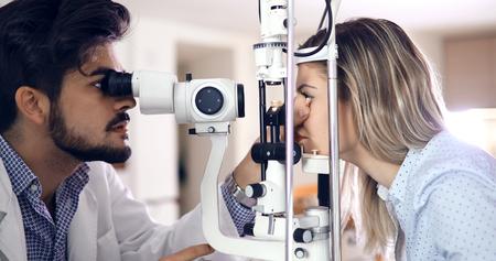 Attentive optometrist examining female patient on slit lamp