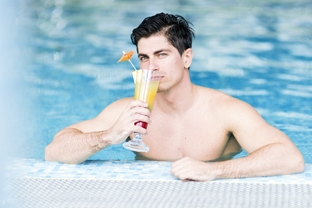 Knappe jonge man die een cocktail in het water drinkt Stockfoto