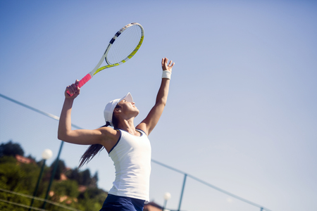 Beautiful female tennis player serving Foto de archivo