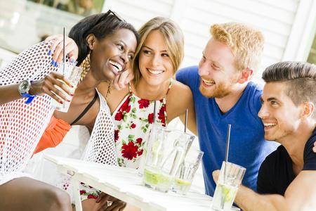 Gelukkige jonge mensen lachen een wezen gelukkig aan een tafel Stockfoto