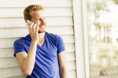 Happy red haired handsome man using phone and smiling Stock Photo