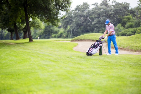 Golfer selecting appropriate club Stock Photo - 91387489