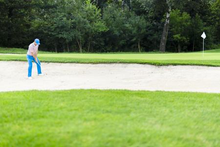 Golfspeler die een bunkerschot neemt