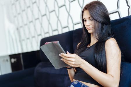 Beautiful young woman using a tablet Reklamní fotografie - 91387535