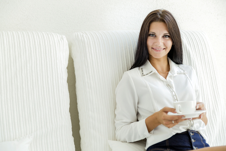 Beautiful woman sipping coffee from a white cup Stock Photo