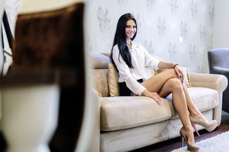Elegante en sexy vrouwenzitting op een bank in een luxueuze ruimte Stockfoto