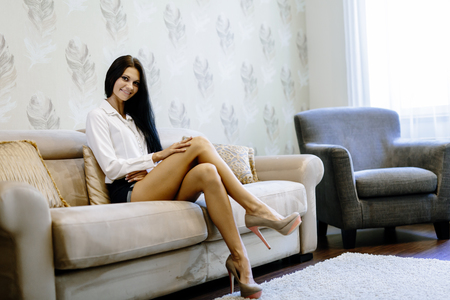 Elegante e sexy mulher sentada em um sofá em um quarto de luxo