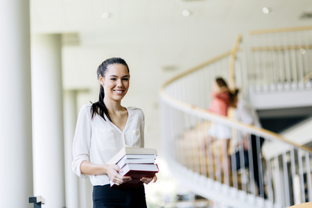 Beautiful woman holding books in a library