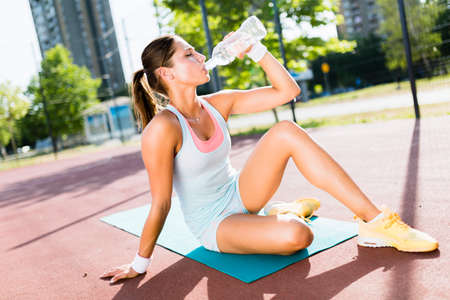 Young beautiful woman drinking water after exercise in a city tr Stock Photo