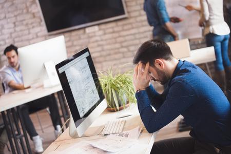 Overwerkte uitgeputte kantoormedewerker die op kantoor werkt