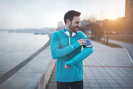Handsome jogger listening to music
