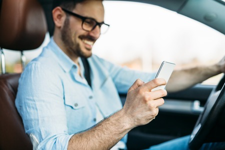 man using phone while driving the car 写真素材