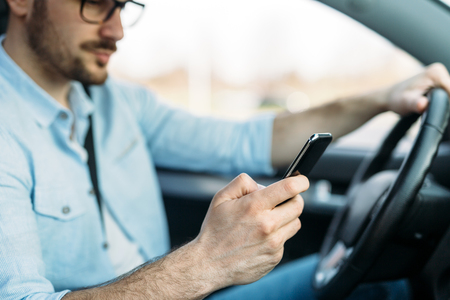 Businessman ignoring safety and texting on mobile phone while driving