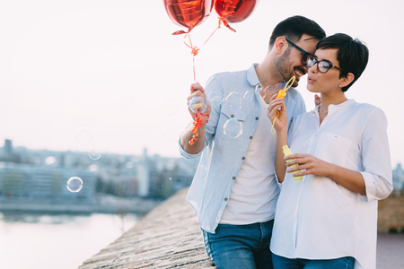 Couple in love holding red baloons hearts on valentine day