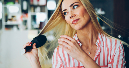 Attractive smiling woman brushing her hair Stock Photo