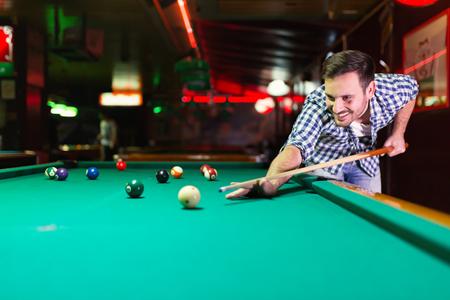 Hansome uomo che gioca a biliardo nel bar da solo Archivio Fotografico - 91968085